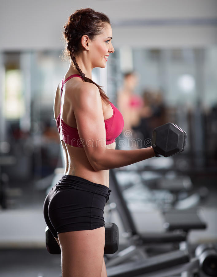Woman doing biceps curl with dumbbells. Athletic woman doing biceps curl with dumbbells in the gym stock photos