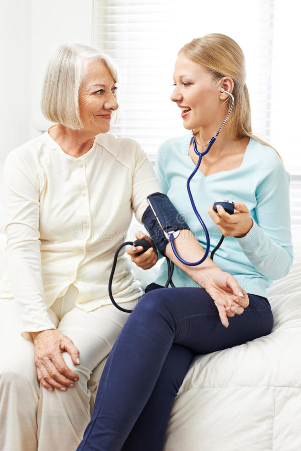 Woman doing blood pressure monitoring. For senior women at home stock photos