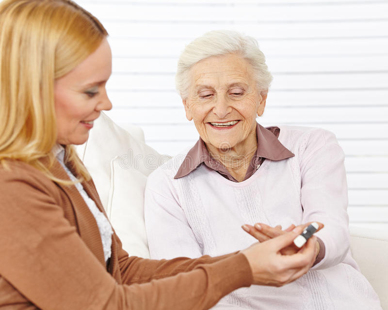Woman doing a blood sugar. Measurement for senior citizen with diabetes stock photography