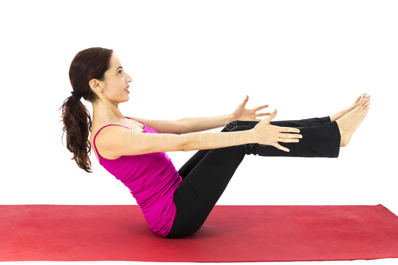 Woman doing boat pose in yoga royalty free stock photography