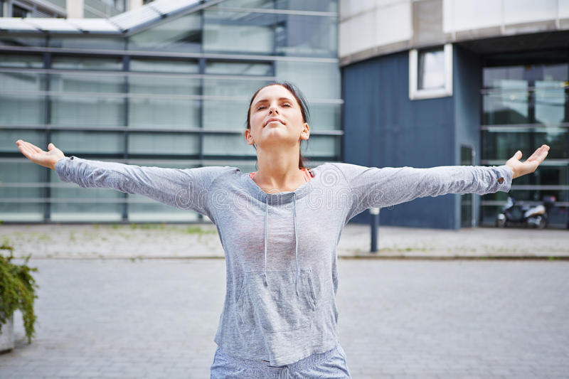 Woman doing breathing exercise in city stock photography