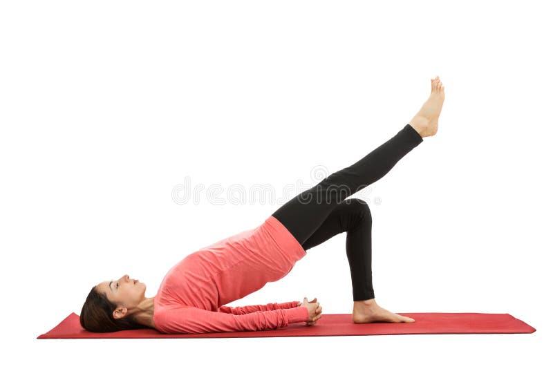 Woman doing bridge pose with leg extension stock image