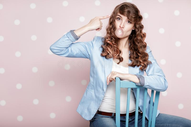 Woman doing bubble with chewing gum. Attractive curly woman doing bubble with chewing gum royalty free stock photos