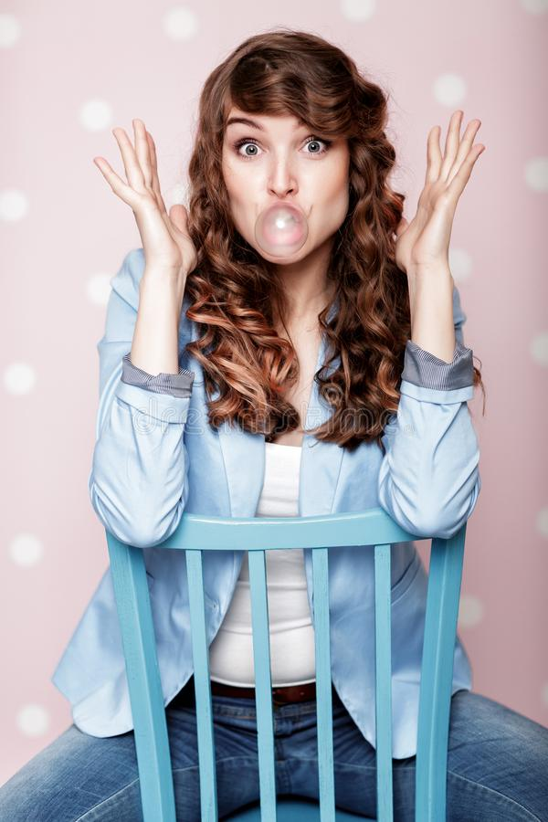 Woman doing bubble with chewing gum. Attractive curly woman doing bubble with chewing gum stock images