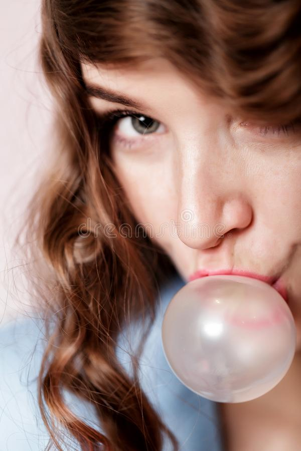 Woman doing bubble with chewing gum. Attractive curly woman with freckles doing bubble with chewing gum close-up stock images