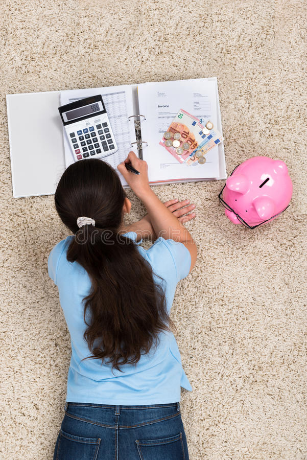 Woman Doing Calculation At Home. Young Woman Lying On Carpet Doing Calculation At Home royalty free stock image