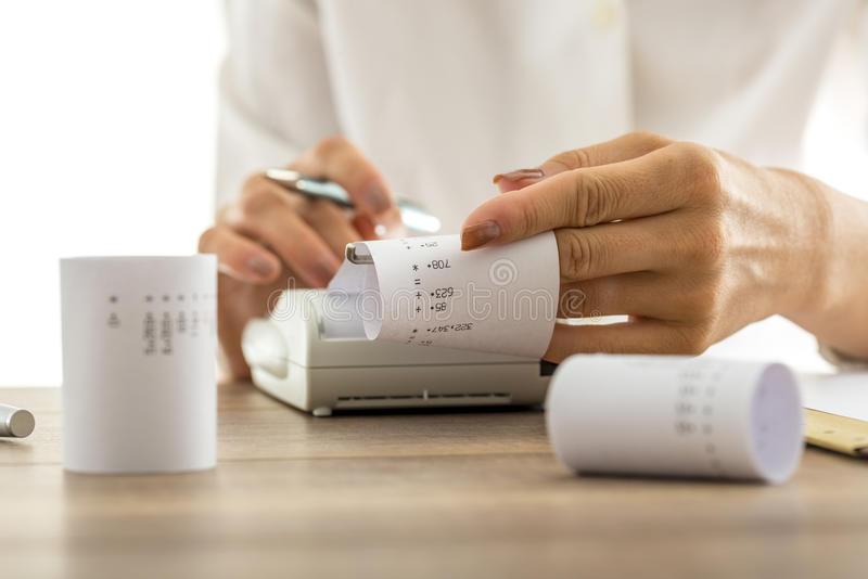 Woman doing calculations on an adding machine stock photos