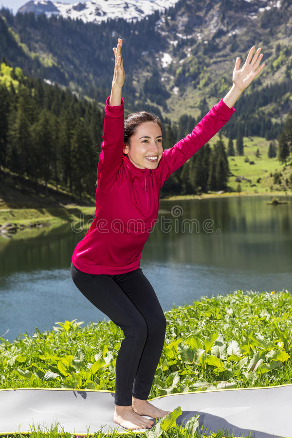 Woman doing chair pose outdoors royalty free stock image