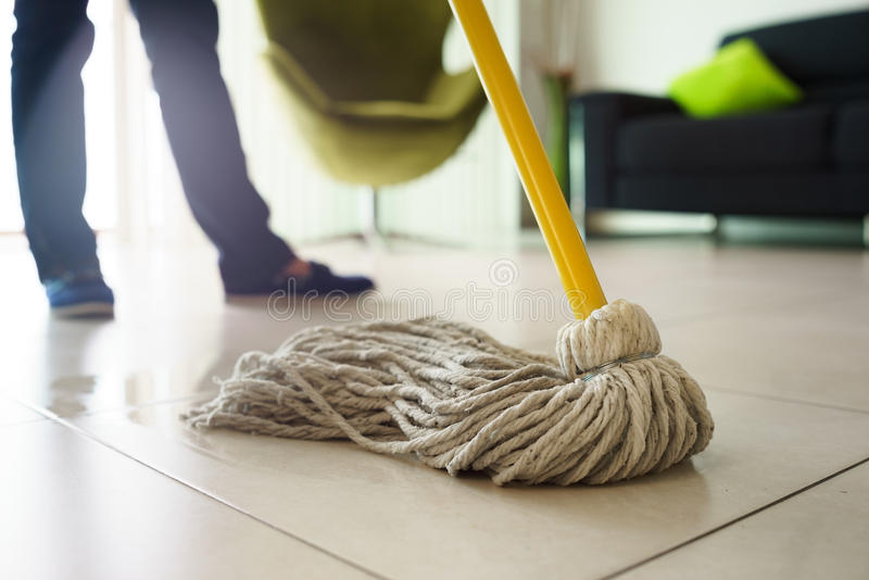 Woman Doing Chores Cleaning Floor At Home Focus on Mop. Woman at home, doing chores and housekeeping, wiping floor with water in living room. Focus on floor and royalty free stock images