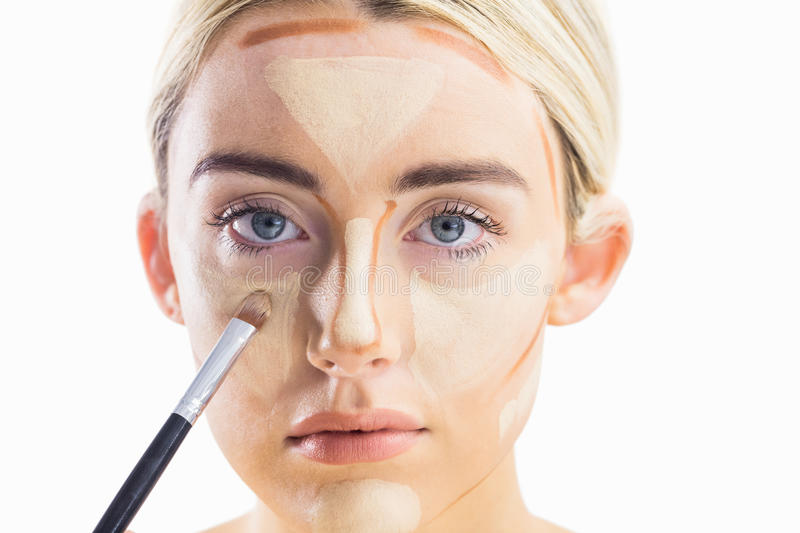 Woman doing contouring on her face royalty free stock photo