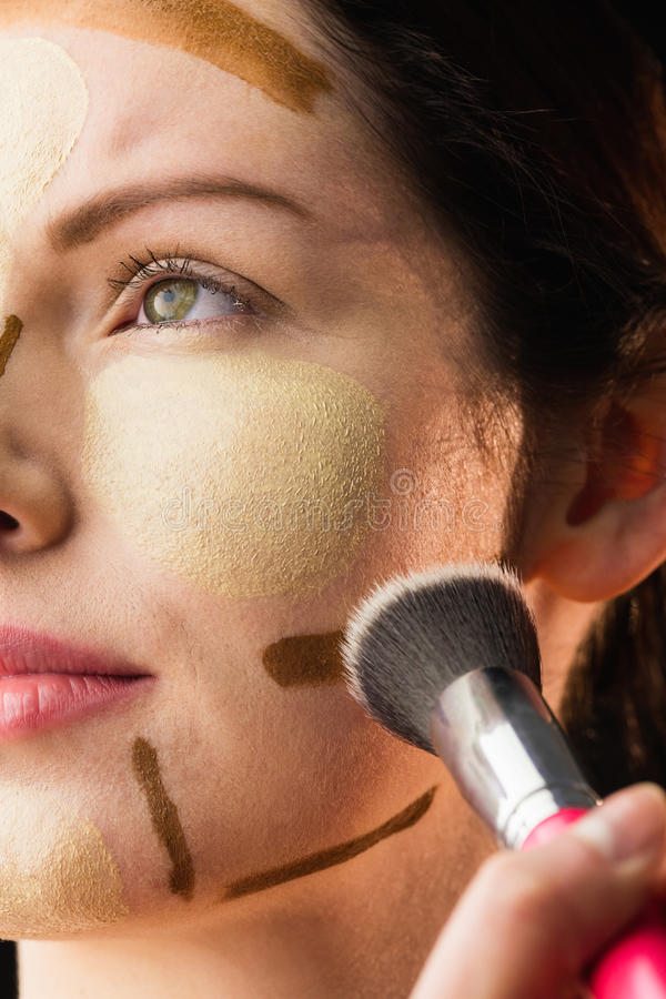 Woman doing contouring on her face stock images