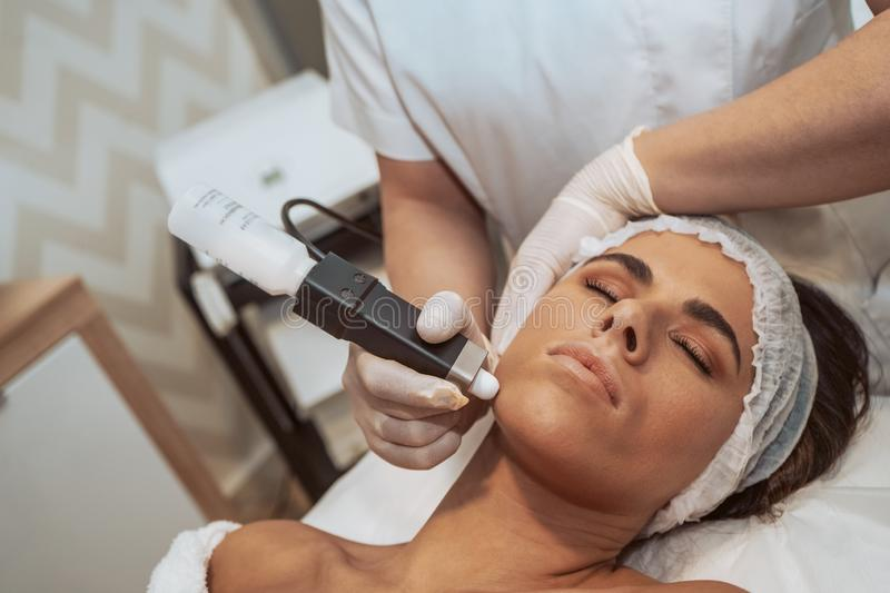 Woman doing cosmetic treatments. Woman getting cosmetic procedures at beauty center stock photos