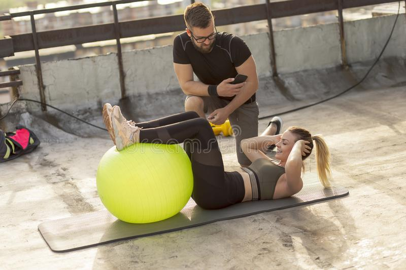 Woman doing sit ups. Woman doing crunches with legs lifted on a pilates ball with the supervision of her personal fitness instructor royalty free stock photo