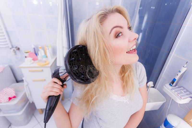 Woman doing curls with hairdryer diffuser stock photos