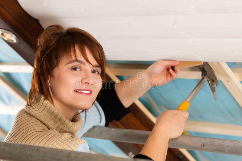 Woman doing dry walling, working. Under a roof slope royalty free stock photography