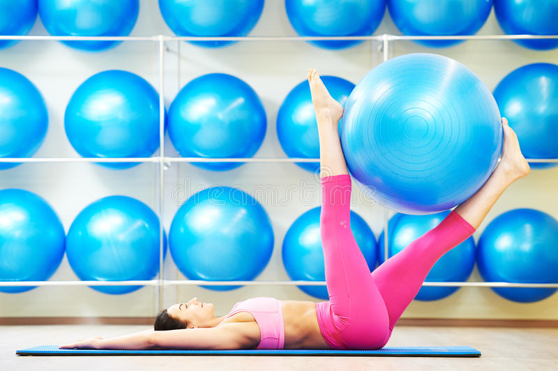 Woman doing exercise with fitness ball. Woman lying on the fitness mat lifting exercise ball using her legs as part of workout routine stock photo
