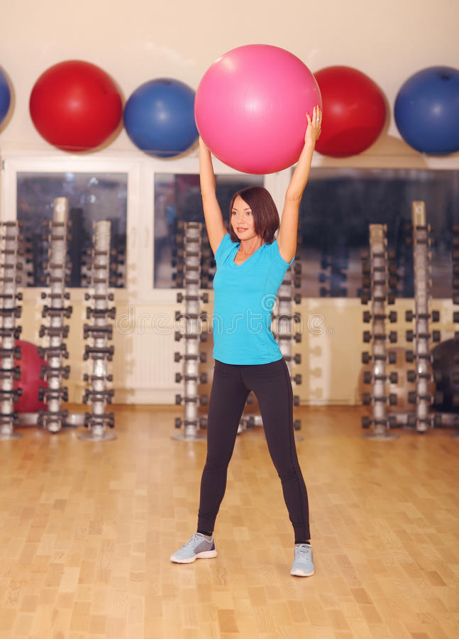 Woman doing exercises with pink fit ball in fitness gym class. Fitness ball helps women get a toned, tight stomach and strong core royalty free stock images