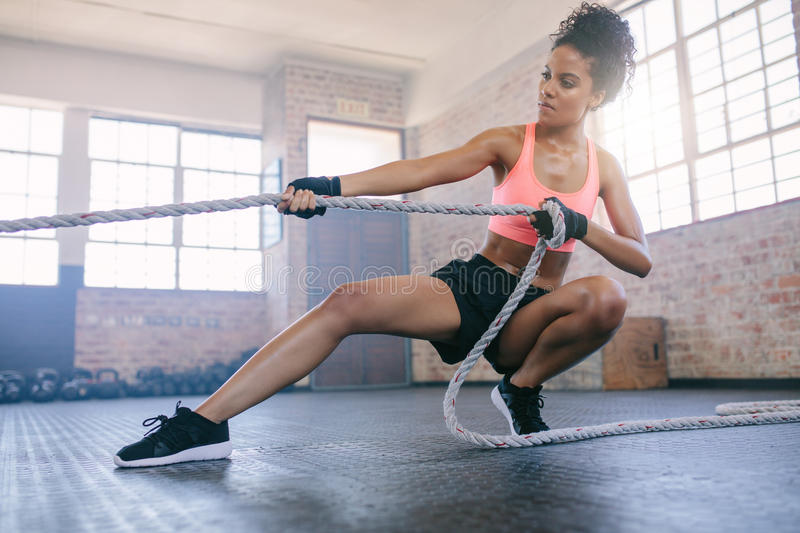 Woman doing exercises with rope at a gym stock images