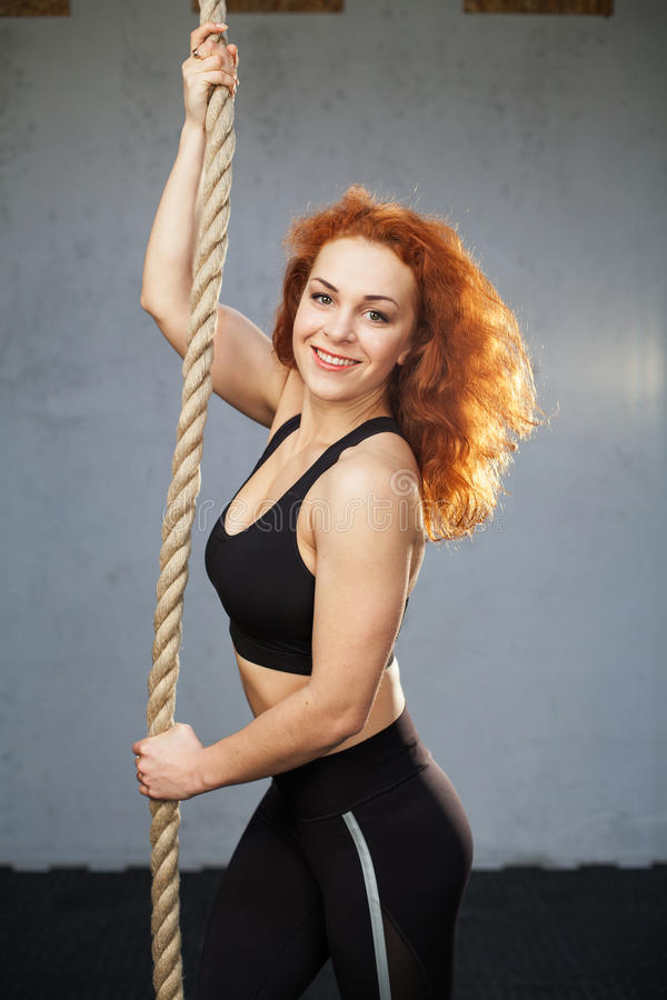 Woman doing exercises with a rope. Young fitness woman doing exercises with a rope at the gym stock photography