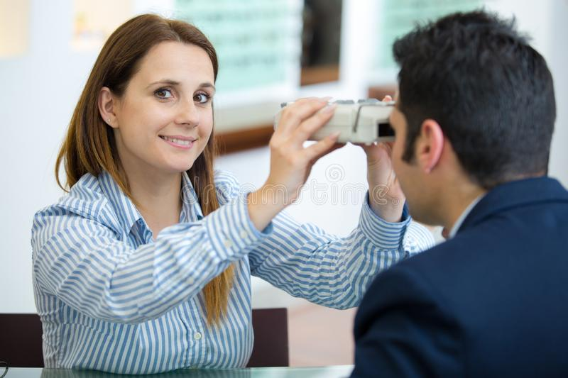 Woman doing eye test with optometrist in eye sight clinic royalty free stock image