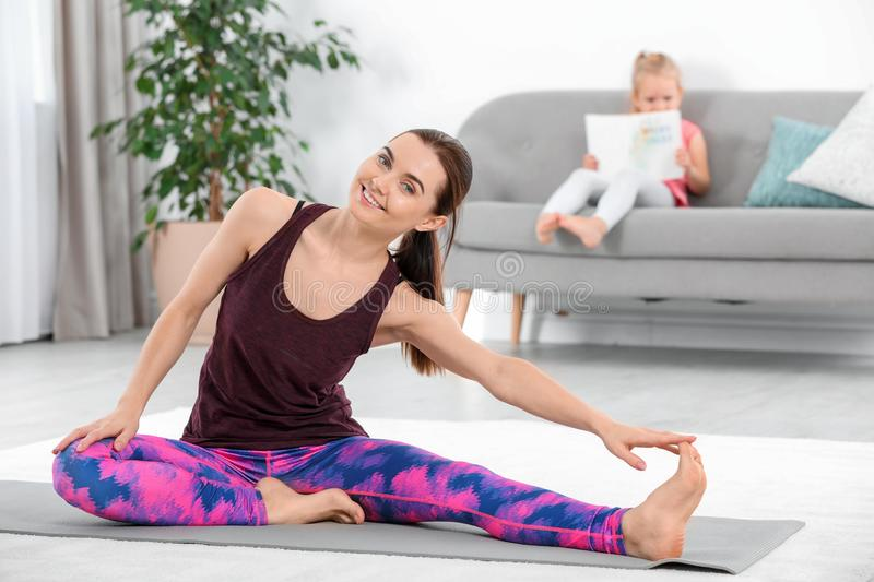 Woman doing fitness exercises while her daughter sitting o royalty free stock images
