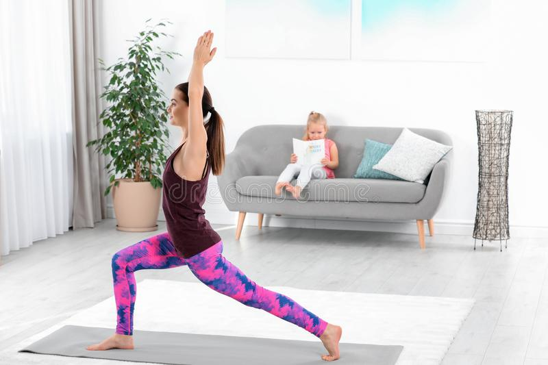 Woman doing fitness exercises while her daughter sitting on sofa stock images