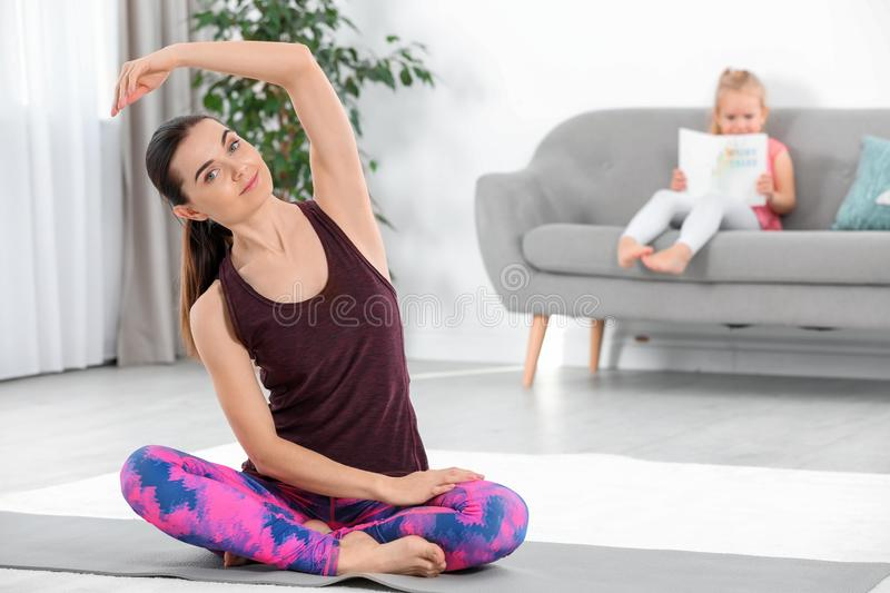Woman doing fitness exercises while her daughter stock photos