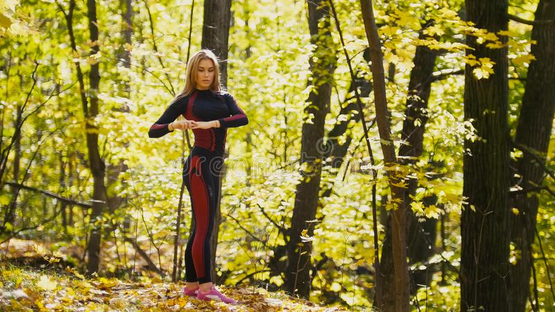 Woman doing fitness exercises outdoor. Female stretching in autumn forest. Slim girl at workout stock image