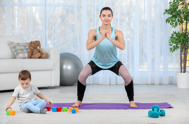 Woman doing fitness exercises together with son stock photography