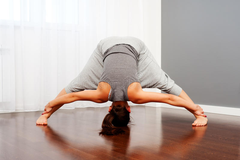Woman doing flexibility exercise in room royalty free stock image
