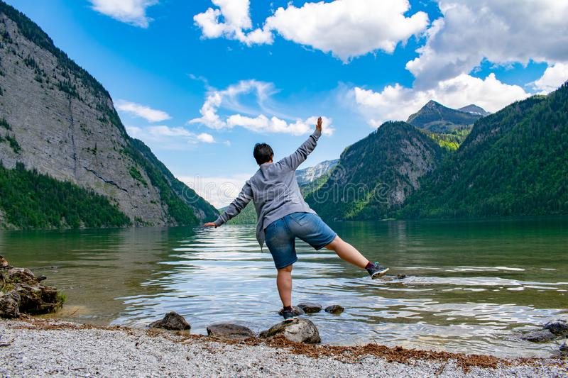 Woman doing gymnastics on the shores of the Königssee royalty free stock image