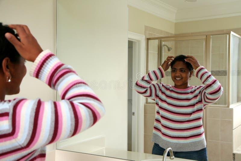 Woman Doing Hair in Mirror stock photo