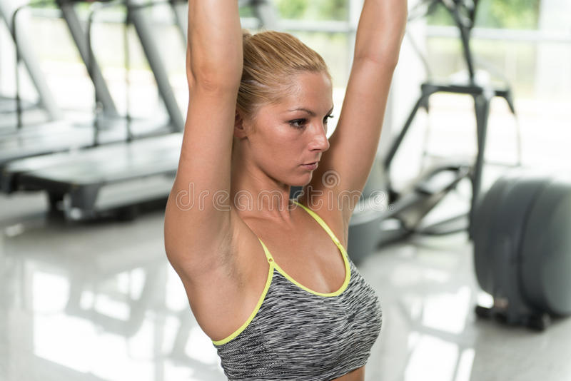 Woman Doing Heavy Weight Exercise For Back. Young Fitness Woman Working Out Back On Machine In Fitness Center stock photo