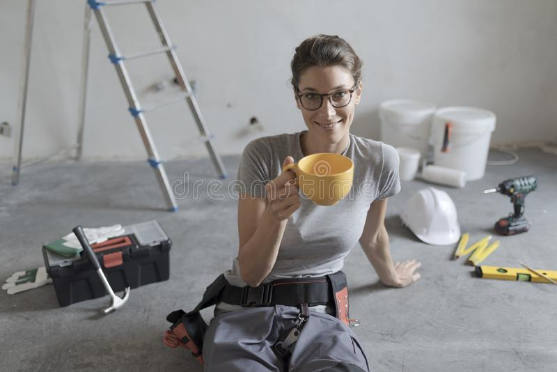 Woman doing a home renovation and having a coffee break. Young smiling woman having a coffee break and sitting on the floor, she is doing a home renovation royalty free stock photos