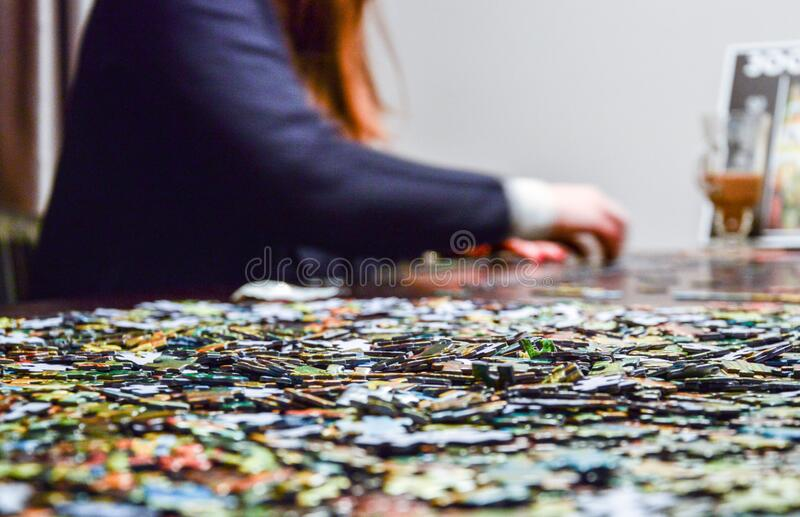 Woman doing jigsaw puzzle royalty free stock images