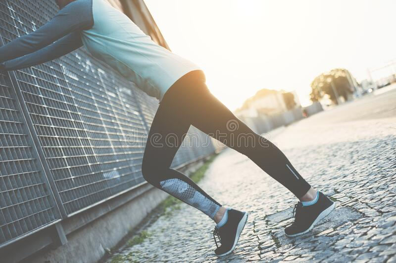 Sporty woman doing legs warming exercise, safety stretching before running. Woman doing legs warming exercise, safety stretching before running stock photography