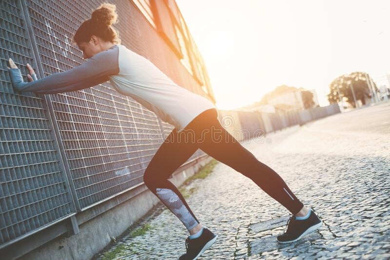 Young woman doing legs warming exercise, safety stretching before running on the street. Woman doing legs warming exercise, safety stretching before running on stock photos