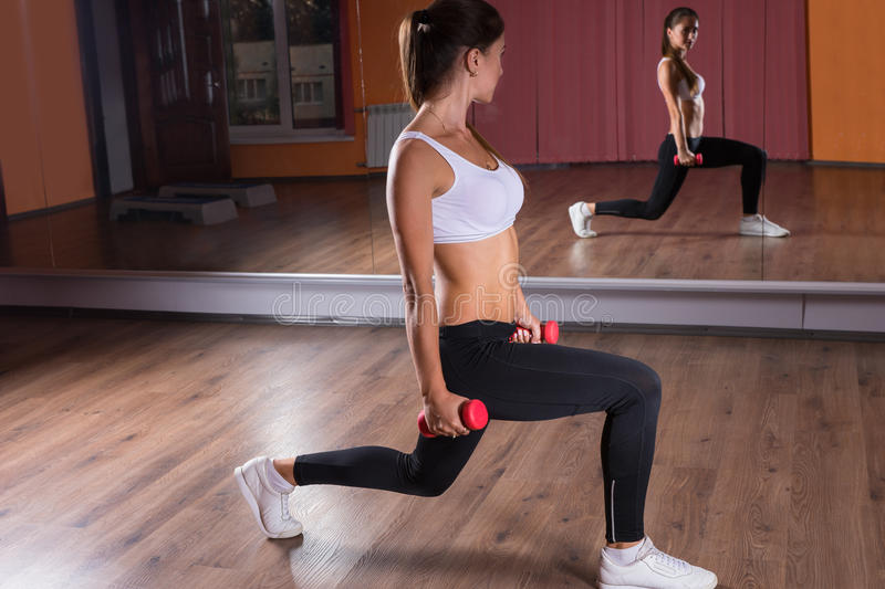 Woman Doing Lunges with Hand Weights in Studio stock photos
