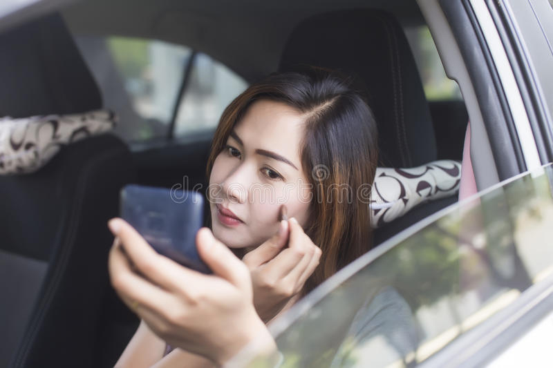 Woman in doing make up in car royalty free stock photography