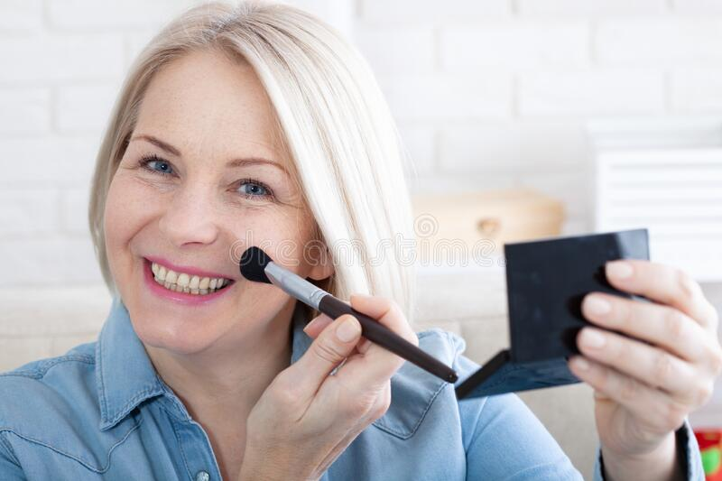 Woman is doing makeup in front of the mirror royalty free stock image