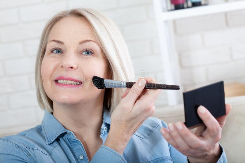 Woman is doing makeup in front of the mirror stock images