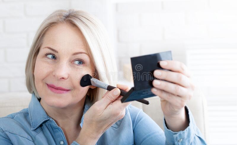 Woman is doing makeup in front of the mirror stock photos