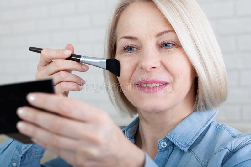 Woman is doing makeup in front of the mirror royalty free stock images