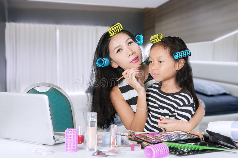 Woman doing makeup with her daughter at home stock photo