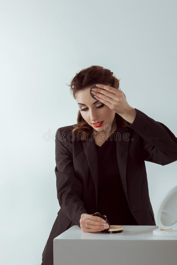 Woman doing makeup at the workplace stock images