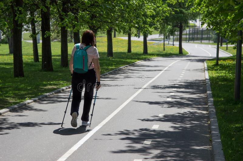 Woman doing nordic walking with a summer park on a sunny day. stock photo