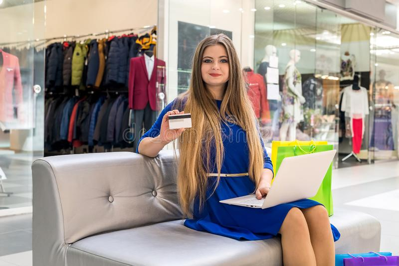 Woman doing online shopping with credit card in hands stock photos