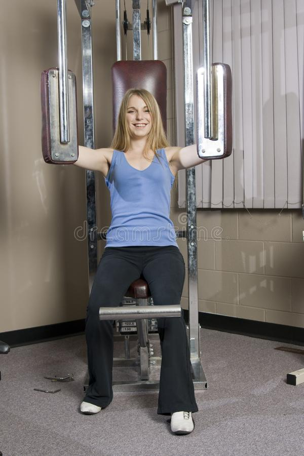 Woman doing pec workout royalty free stock photography