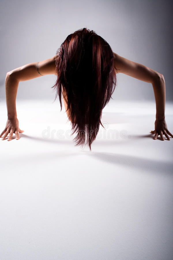 Woman doing press or push ups. Young woman with long hair doing push or press ups on white studio background with copy space stock images