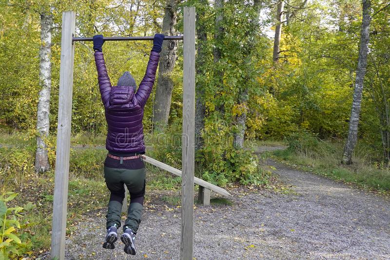 Woman doing pull ups outdoor in park. Middle aged female enjoying beautiful autumn day, and increase her welfare by outdoor activities royalty free stock photo